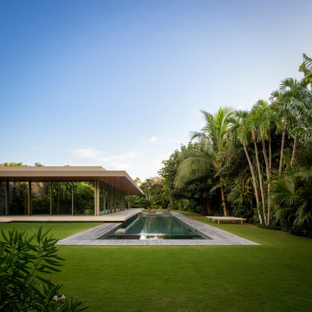 The glass box, which houses the social area, projects itself over the pool, intensifying the feeling that the house is floating above the ground.