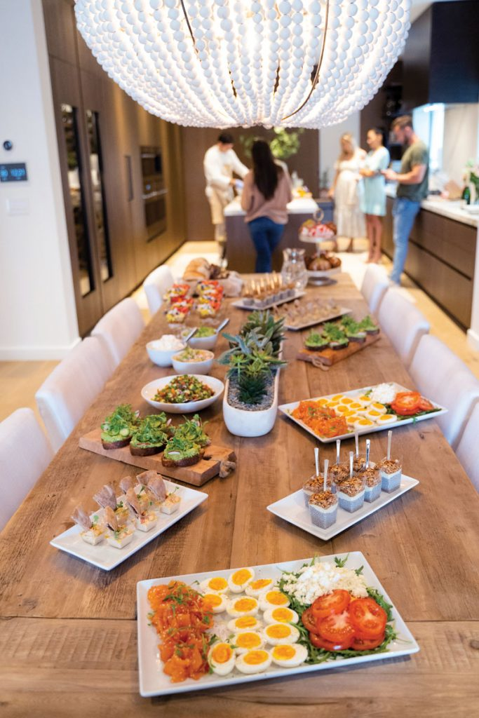 The couple's kitchen was a hub of activity, with many attendees congregating there before filling their plates. The space includes a table made from an old door and a beaded stone and ceramic chandelier.