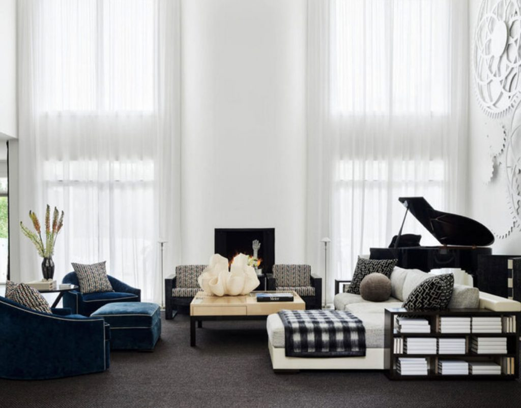 A soaring contemporary living room in Nashville features a large art installation of wooden gears purchased at the renowned Swan Ball benefiting the Cheekwood Botanical Garden. Miles of white cotton voile from Rubelli covers the windows. All is grounded by a sea of charcoal broadloom from Stark Carpet. <br/> Photo by Douglas Friedman